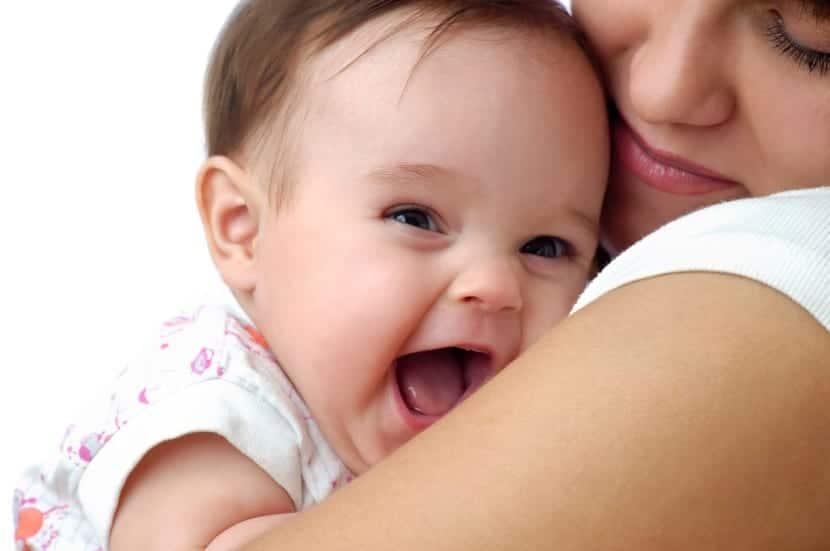 bebé riendo en brazos de su mama