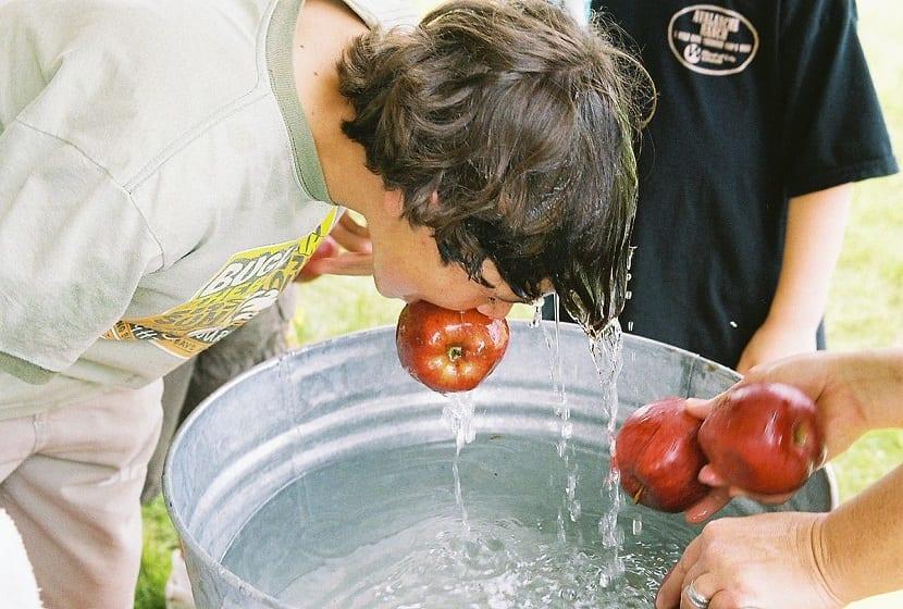Niño jugando a coger la manzana sin manos