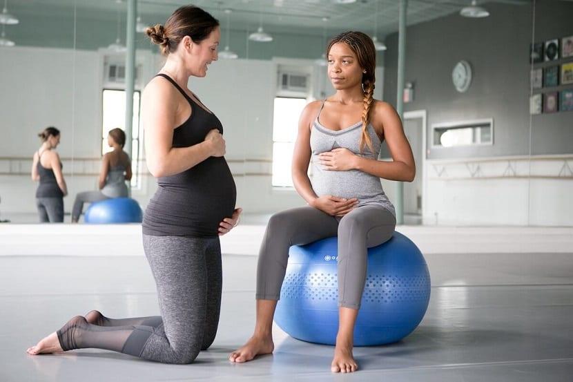 Embarazada hace ejercicio sobre balón de fitness