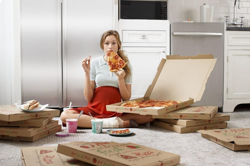 Mujer embarazada comiendo pizza