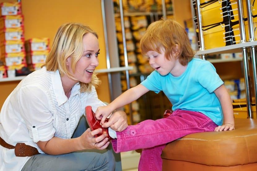 Madre comprando zapatos a su hija