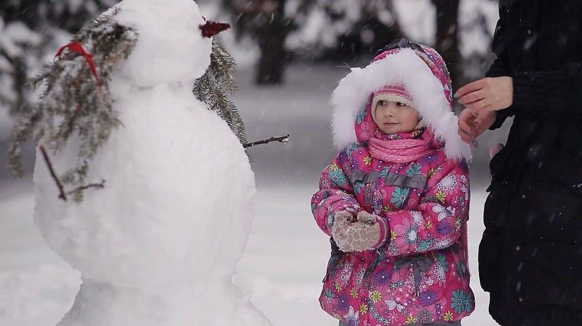 Niña haciendo un muñeco de nieve