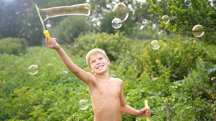 Niño haciendo pompas de jabón