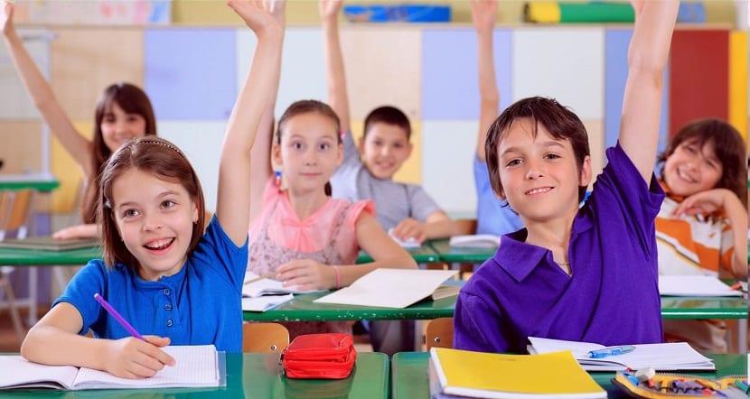 Niños en clase con la mano levantada