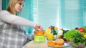 Mujer embarazada preparando zumo