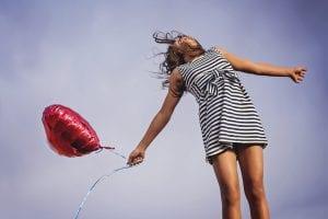 Una joven feliz, tras recibir como regalo un globo en forma de corazón.