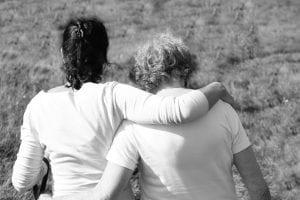 Madre se consuela con un familiar por la muerte de su hijo.
