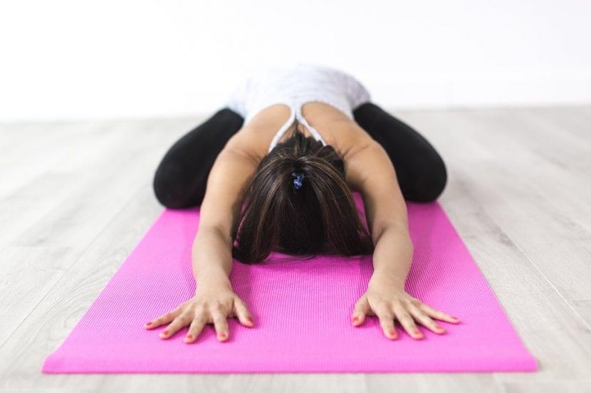Madre practicando meditación en su clase de yoga.