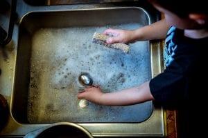 Niño con TOC lava repetidas veces los utensilios de cocina.
