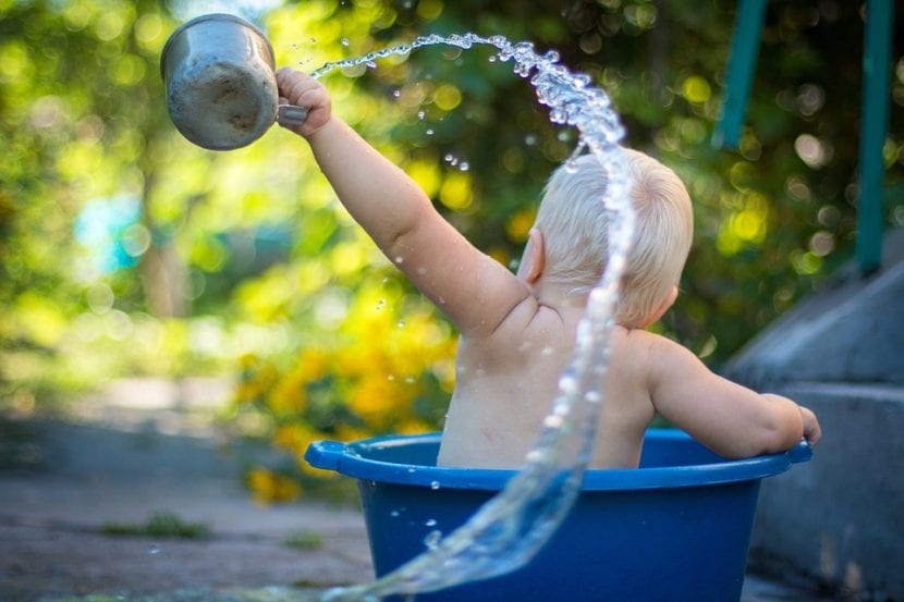 Un bebé toma un baño en una tina al aire libre.