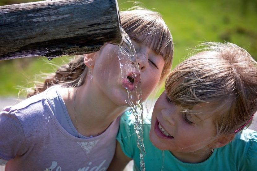 Niñas beben agua pura en medio del campo.