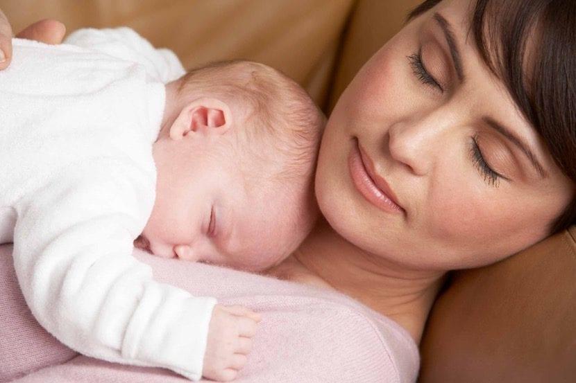 Bebé duerme plácidamente sobre el pecho de su madre.