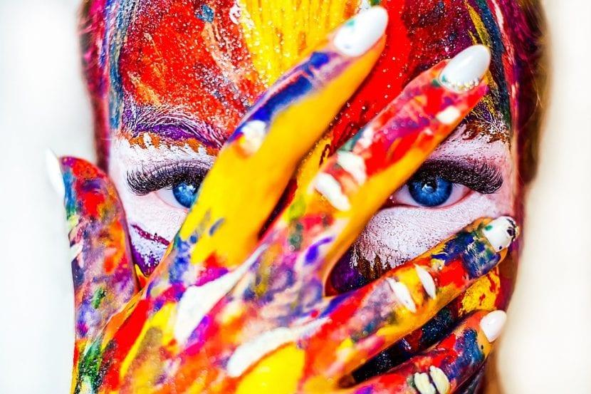 Mujer se manifiesta por su libertad pintándose la cara con colores arcoiris.