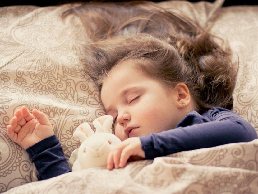 Niña duerme sola en su cama agarrada a su peluche.