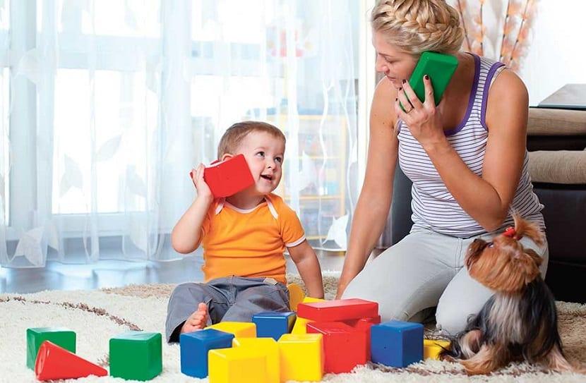 Madre y bebé jugando a hablar por teléfono