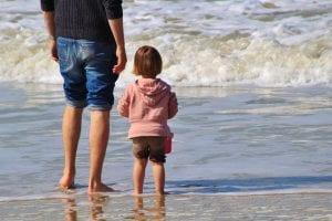 Padre e hija disfrutan de un día de playa juntos.