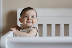 preciosa bebe sonriente en su cuna