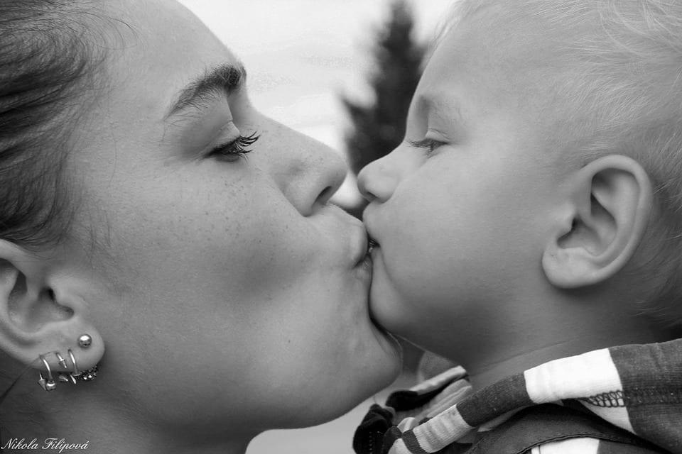 Madre feliz con su bebé demuestra su afecto besándole la boca.