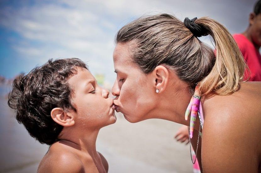 Durante un agradable día de playa, madre besa a su hijo en los labios.