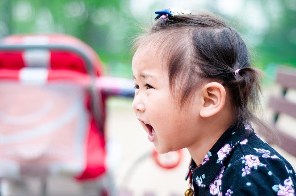 Niña en el parque grita a su madre tras una reprimenda.