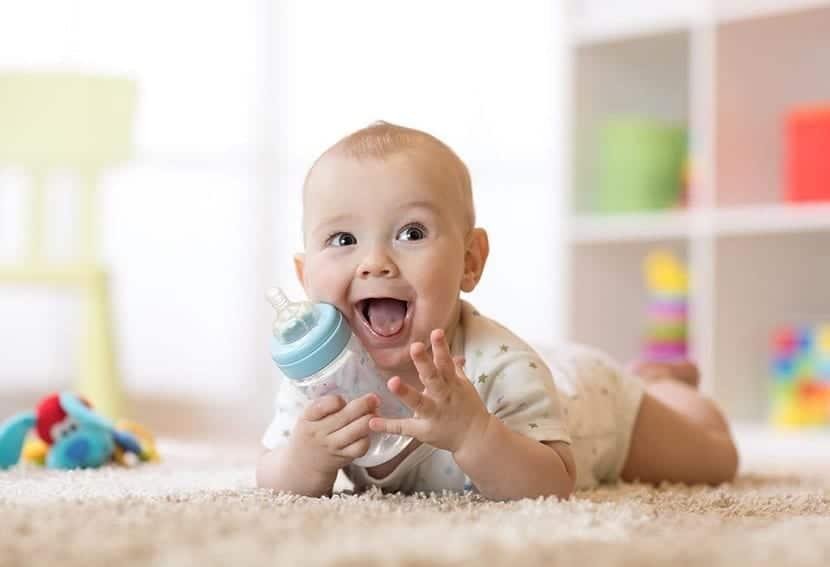 Risueño bebé con un biberón
