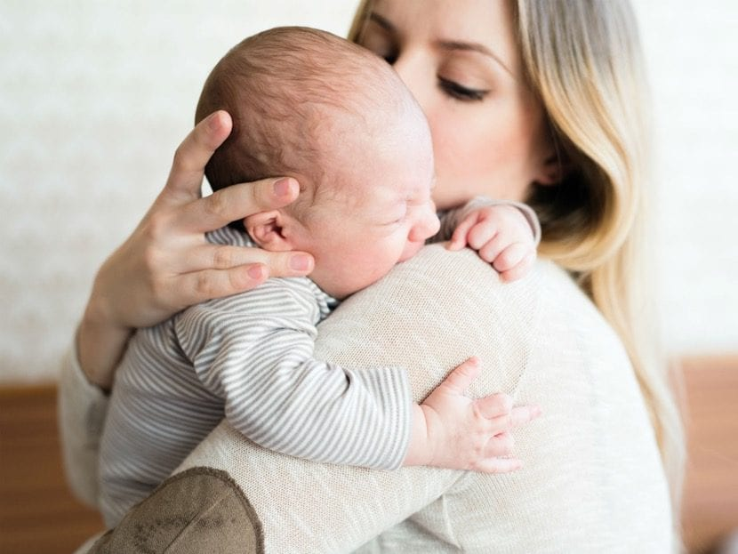Madre consuela a su bebé que llora por infección en el oído.