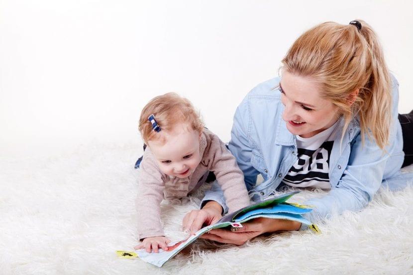 Madre se divierte leyéndole un cuento a su hija pequeña.