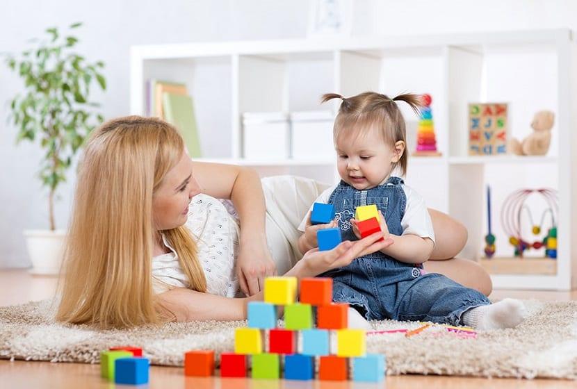 Niñera jugando con una bebé