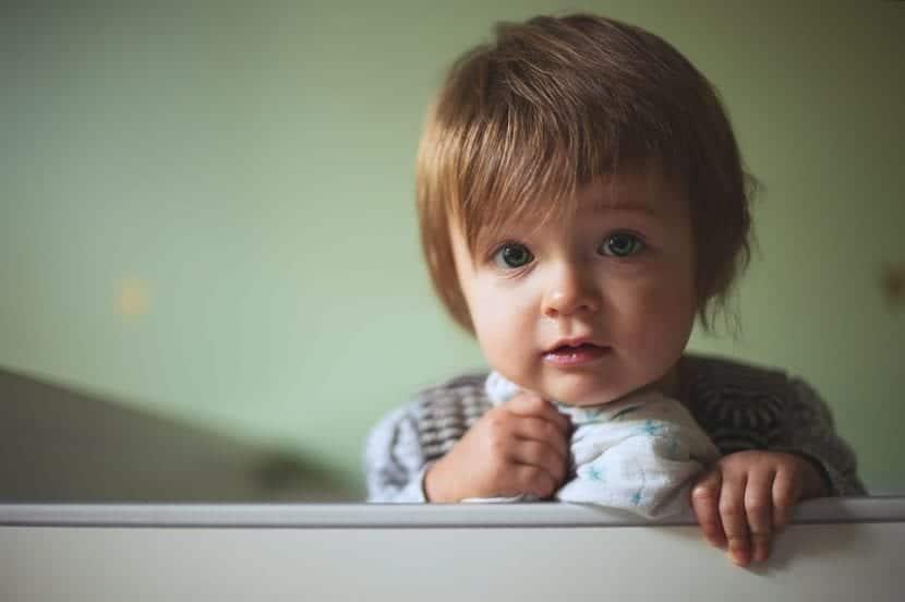 El niño se muestra intranquilo y deseoso por salir de su cuna.