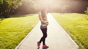 Embarazada camina por un parque.