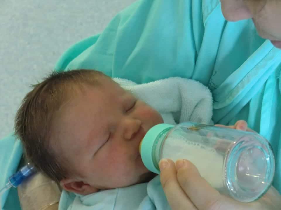 Bebé recién nacido toma biberón.