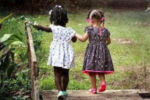 Dos amigas pasean juntas de la mano por el campo.