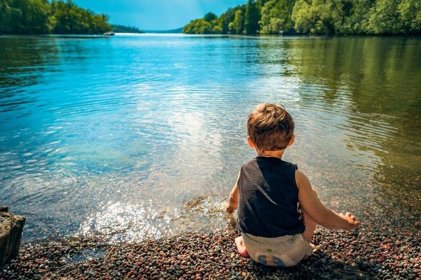 Niño refrescándose en un lago en verano.