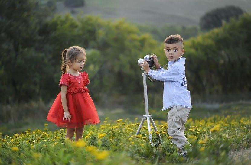 Niños juegan a realizar una sesión de fotos con bonita ropa.