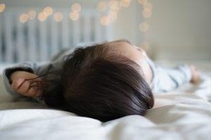 Bebé duerme en la cama de sus padres.