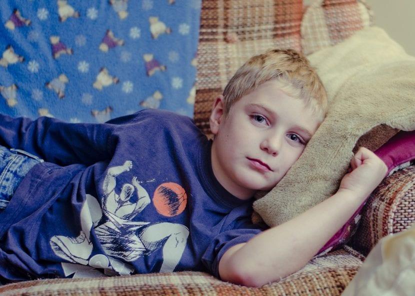 Niño con fiebre tumbado en el sofá, infectado por mononucleosis.