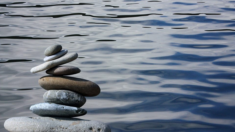 Símbolo zen. Piedras apiladas junto al agua.