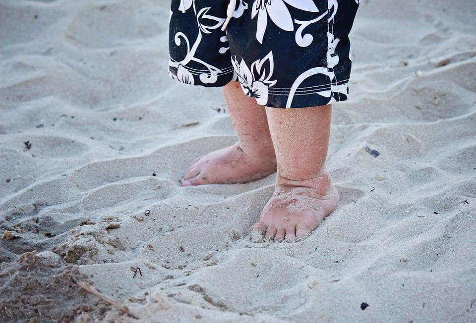 Bebé descalzo en la playa.