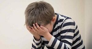 Niño con depresión se encuentra agobiado y angustiado.