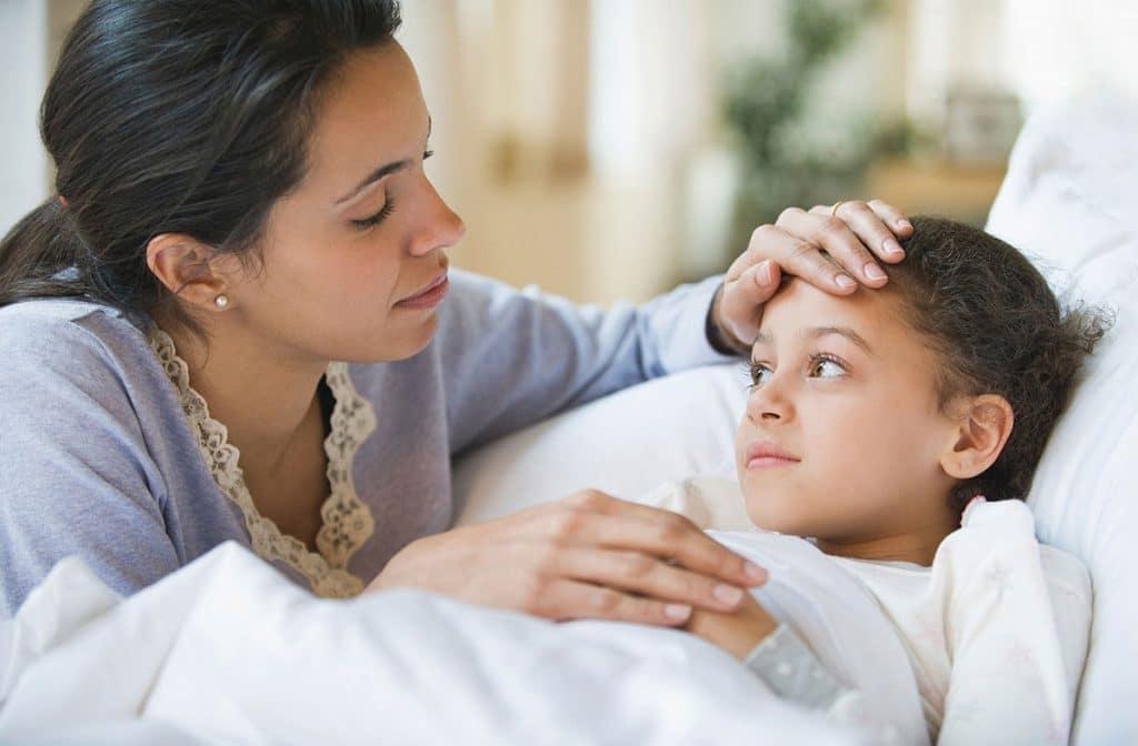 Madre toma la temperatura a su hija