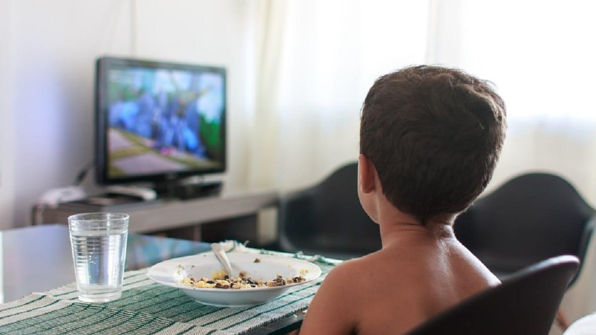 Niño come frente al televisor
