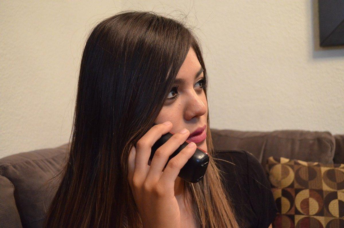 chica sosteniendo un teléfono fijo inalámbrico duo
