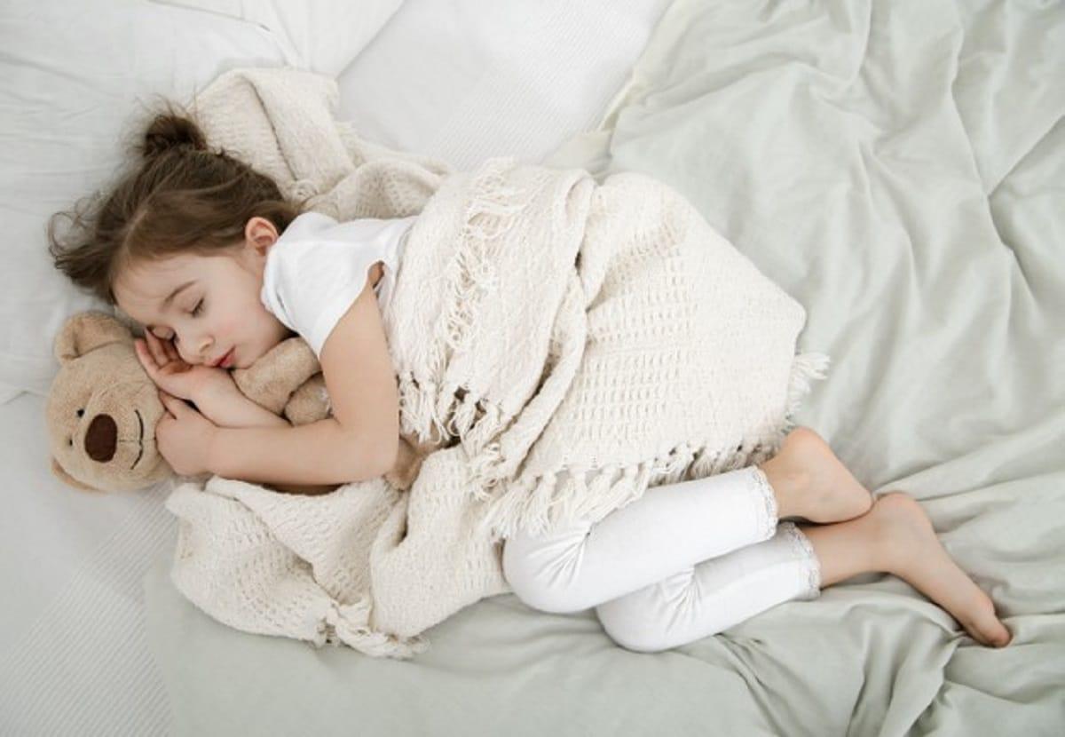 Niña dormida con un oso de peluche