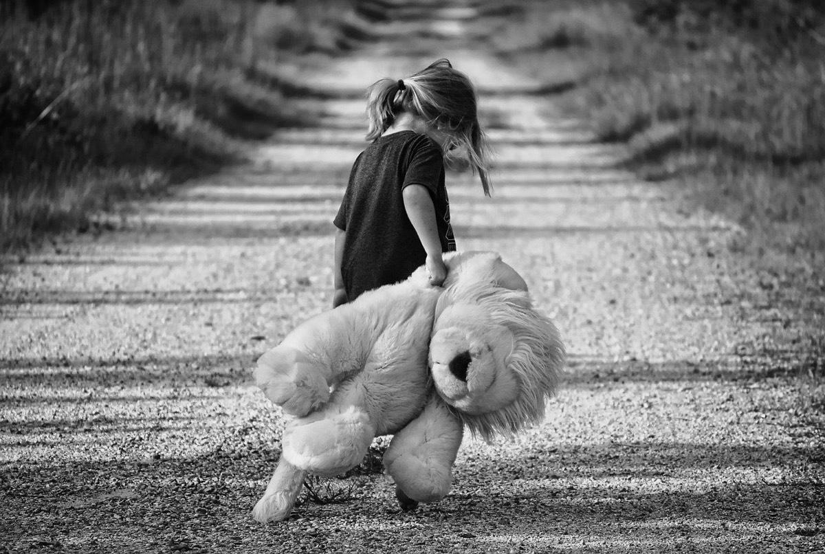 niña caminando con peluche