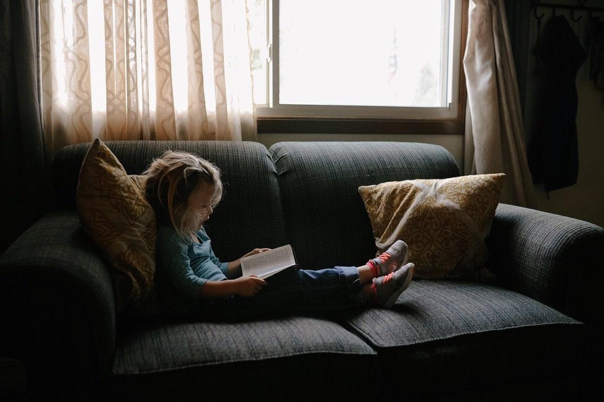 Niña leyendo en el sofá