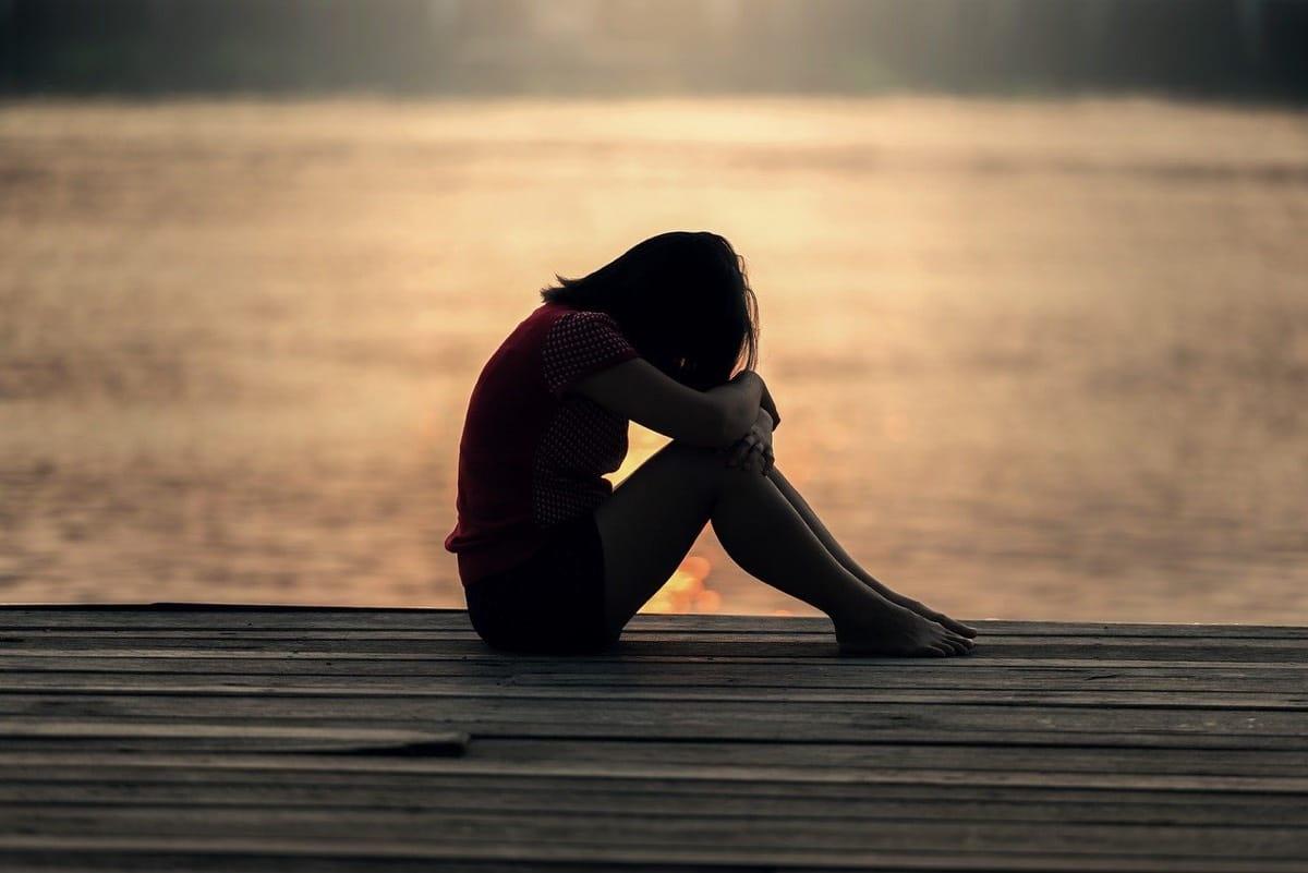 niña triste y sola en un muelle