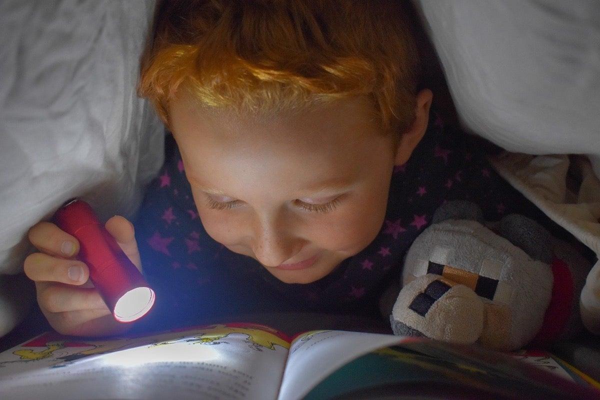 Niño leyendo en la cama
