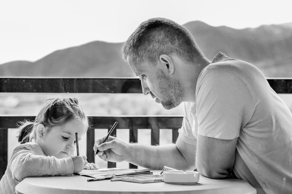 Padre ayudando a su hija a pintar