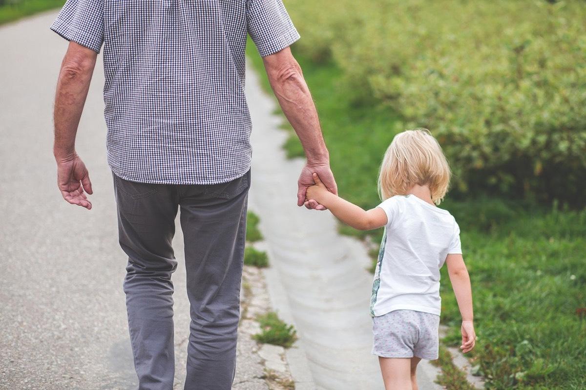 Padre e hija paseando por un camino