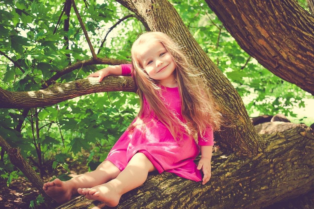 niña feliz subida en árbol
